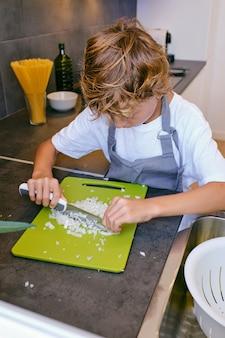 キッチンで料理しながら新鮮なタマネギを切る集中少年