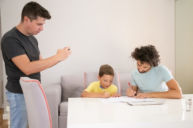 Focused boy doing school home task with help of two dads, writing in papers. man taking picture of his family. family and gay parents concept