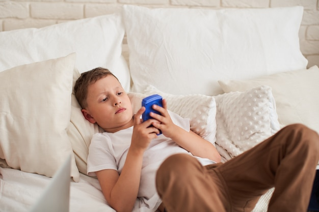 Focused boy is lying on a bed and playing a video game.