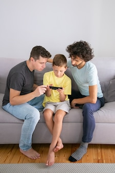 휴대 전화에서 게임을하는 집중된 소년, 그의 두 아빠가 그 근처에 앉아서 돕는다. 세로 샷. 가정 및 통신 개념에서 가족