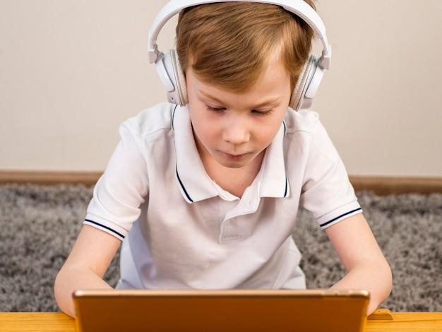 Сосредоточенный мальчик играет на своем ноутбуке