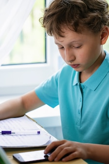焦点を当てた少年はテーブルに座って、スマートフォンを使って宿題をします。