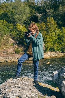 바위 해안에서 사진을 찍는 집중된 소년