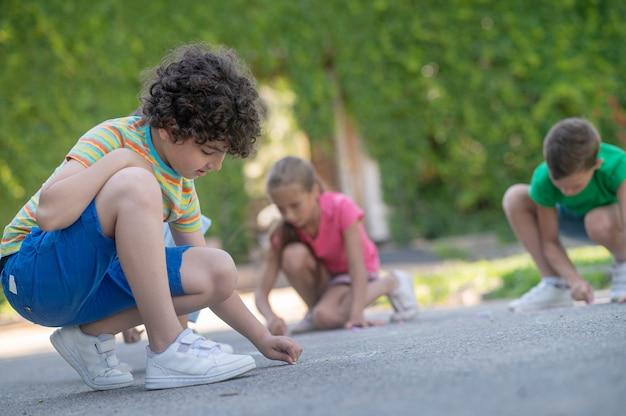 Сосредоточенный мальчик с друзьями рисует на асфальте