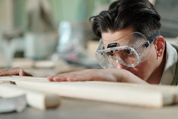 Focused brunette male carpenter in safety goggles checking processed planks after polishing in workshop
