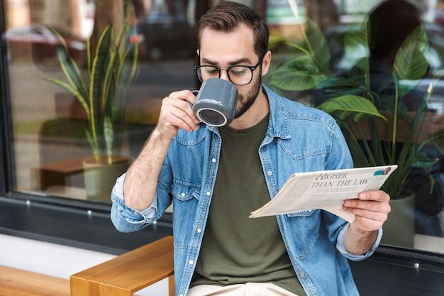 Сосредоточенный брюнетка мужчина в джинсовой рубашке и очках читает газету с чашкой кофе в кафе на открытом воздухе