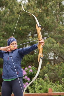 Focused brunette practicing archery