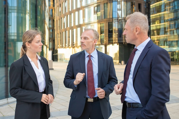 Focused business colleagues wearing office suits, meeting outdoors, standing and talking with city buildings in background. corporate communication concept