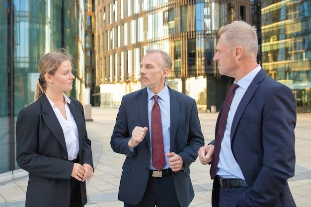 Colleghi di lavoro concentrati che indossano abiti da ufficio, si incontrano all'aperto, stanno in piedi e parlano con gli edifici della città sullo sfondo. concetto di comunicazione aziendale
