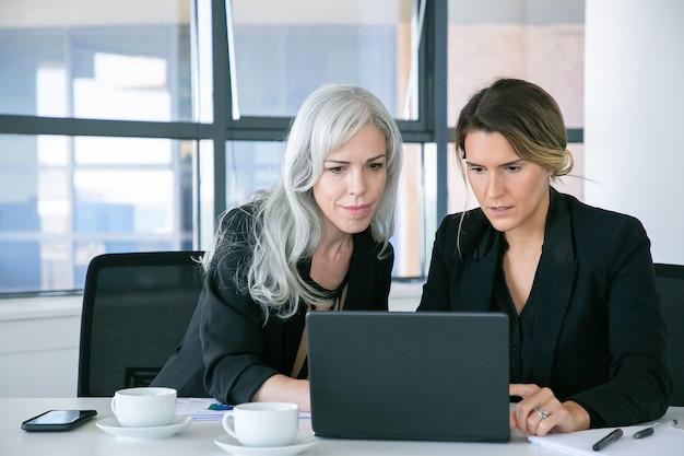 사무실에서 커피 컵 테이블에 앉아있는 동안 노트북 디스플레이보고 집중된 비즈니스 숙 녀. 팀워크와 커뮤니케이션 개념