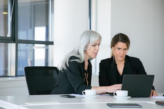 커피 컵과 함께 테이블에 앉아 얘기하는 동안 노트북 콘텐츠를보고 집중된 비즈니스 숙 녀. 팀워크와 커뮤니케이션 개념