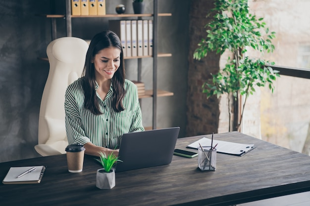 Focused business lady freelancer typing email on laptop at office
