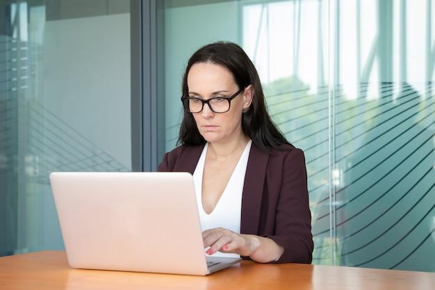 眼鏡とジャケットを着て、オフィスのコンピューターで働いて、テーブルで白いラップトップを使用して焦点を当てたビジネス女性