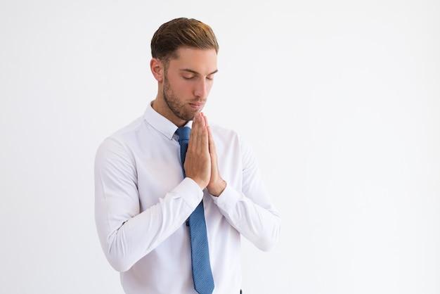 Сосредоточенный деловой человек молиться и держать руки вместе.