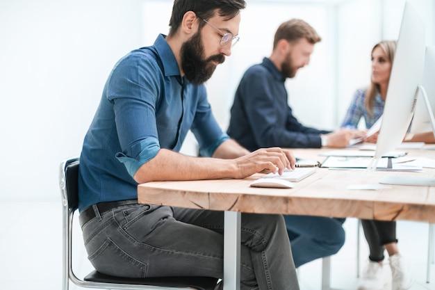 オフィスでコンピューターに取り組んでいる集中ビジネスマン