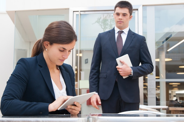 Focused business woman using tablet and coworker standing near