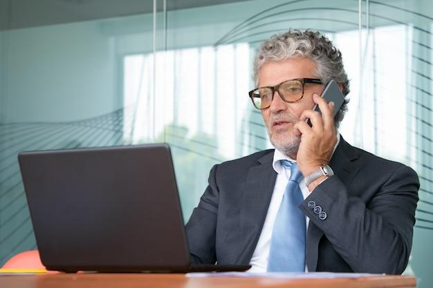 사무실에서 노트북에서 일하고, 휴대 전화에 대한 거래를 논의하는 양복과 안경에 집중된 사업가, 디스플레이를보고