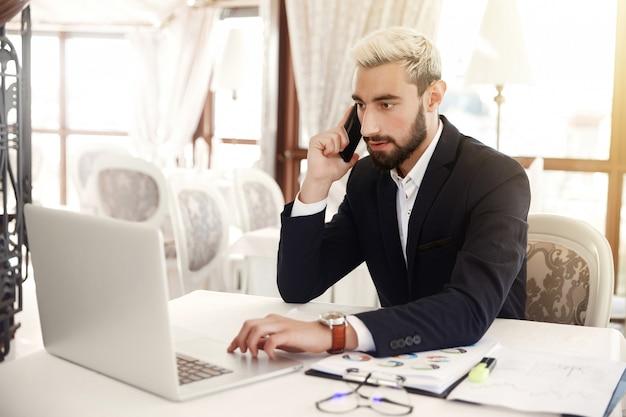 L'uomo d'affari messo a fuoco sta guardando sullo schermo di un computer portatile e sta parlando sul cellulare