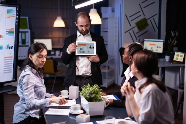 회사 아이디어에서 작업하는 태블릿을 사용하여 회사 그래프 프레젠테이션을 보여주는 집중된 사업가입니다. 다양한 다민족 사업가들이 늦은 밤 사무실 회의실에서 전략을 브레인스토밍