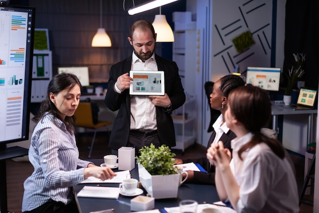 Focused businessman showing corporate graphs presentation using tablet working at company ideas. diverse multi-ethnic businesspeople brainstorming strategy late at night in office meeting room