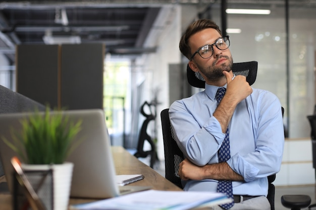 Focused businessman thinking at modern office into report file calculating stock market earnings, startup business.
