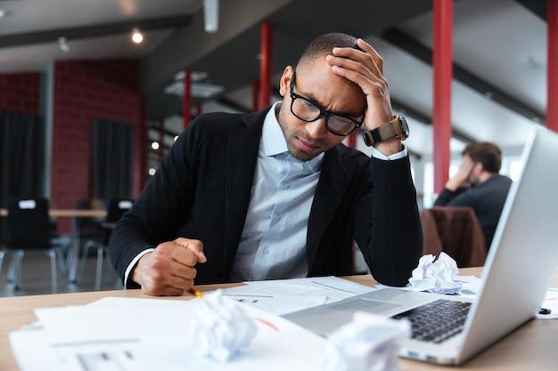 Сосредоточенный бизнесмен думает над ноутбуком