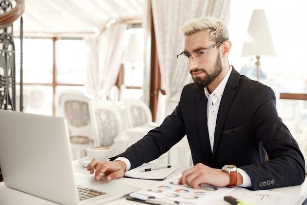 L'uomo d'affari messo a fuoco che indossa gli occhiali sta lavorando al computer portatile al ristorante