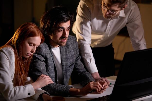Сосредоточенный бизнесмен, работающий с сонными коллегами в офисе в ночное время. бизнес-группа, работающая на компьютере, обсуждение. современный лофт. работая сверхурочно. бизнес-концепция. уверенный бизнесмен.