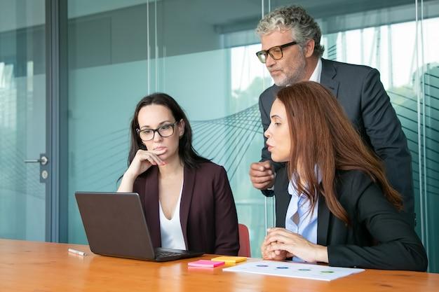 焦点を当てたビジネスマンが座っていると開いているラップトップに立って、画面を見つめています。