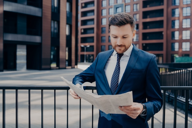 Focused businessperson dressed in suit checking latest newspaper for interesting news, standing outside alone while leaning on black fence next to office plaza buildings, enjoying work break outdoors
