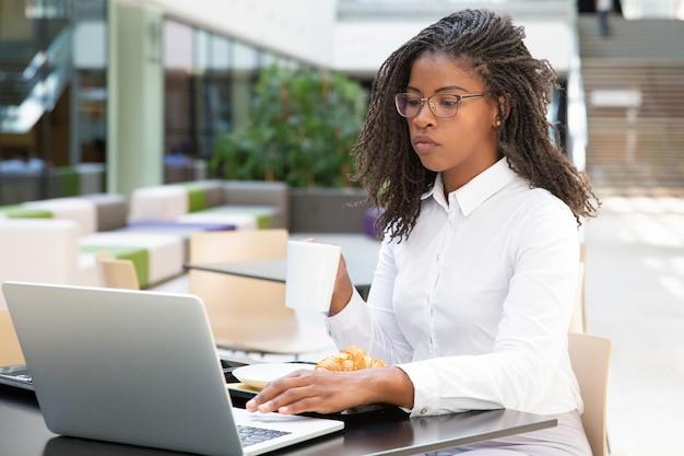 Сосредоточенная коммерсантка выпивая кофе пока работающ
