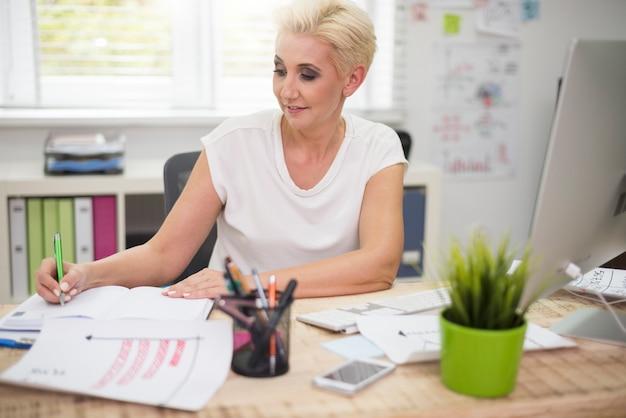Сосредоточенный бизнесвумен, делая заметки