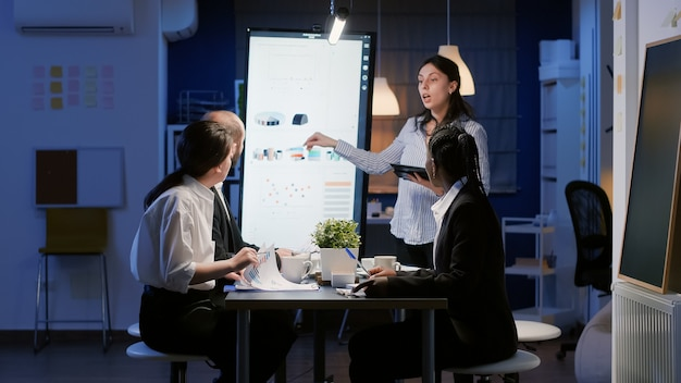 Focused businesswoman pointing management strategy using monitor for presentation