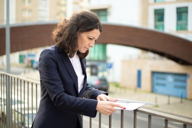 Documenti messi a fuoco della lettura della donna di affari sulla via