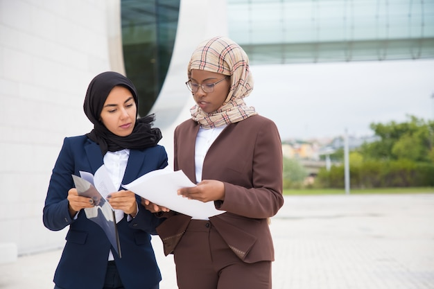 Focused businesswomen walking on street and inspecting documents
