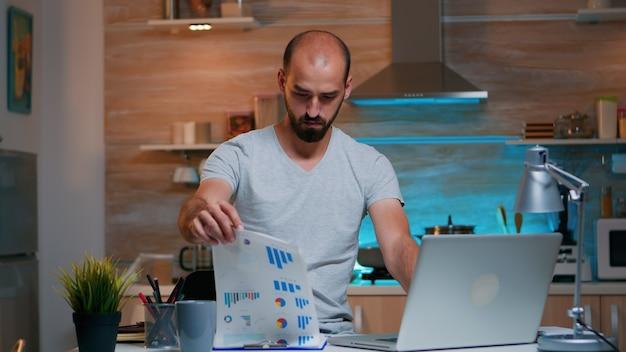 Сосредоточенный занятый предприниматель, проверяющий графику из буфера обмена с помощью ноутбука, глядя на ноутбук, работая дома в полночь. занятый сотрудник, использующий современные технологии беспроводной сети