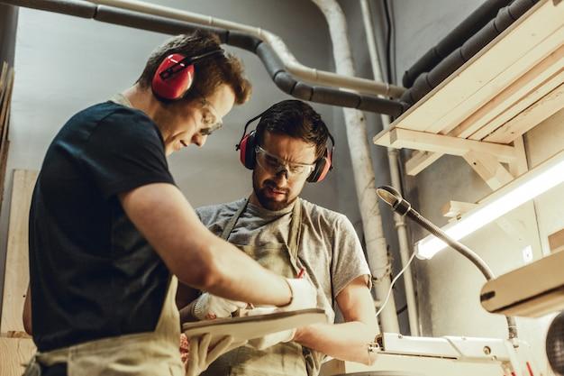 Focused carpenters making sketches in sketchbook