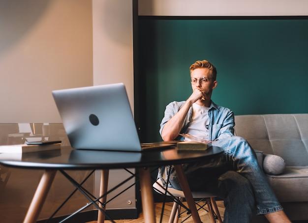 本やノートパソコンで遠く離れて勉強している眼鏡の焦点を当てた白人男性大学生