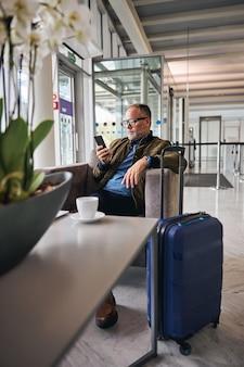 Сосредоточенный кавказский человек, глядя на свой мобильный телефон