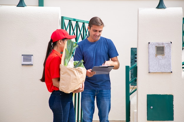 Focused caucasian man standing and signing in order sheet. brunette female courier in red uniform holding paper bag with vegetables from grocery store. food delivery service and post concept