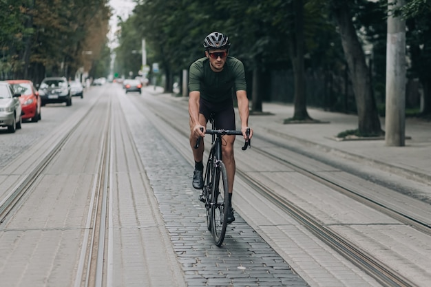 Focused caucasian man wearing safety helmet and mirrored glasses using bike for training on city street. professional cyclist spending free time for outdoors activity.