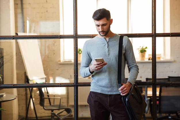 Сосредоточенный кавказский мужчина с бородой, используя мобильный телефон, стоя в современном офисе