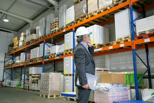 Focused ceo in formal suit and hardhat standing in warehouse and talking on mobile phone