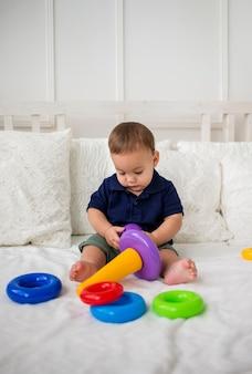白いベッドの上でピラミッドのおもちゃで焦点を当てた子供男の子の研究