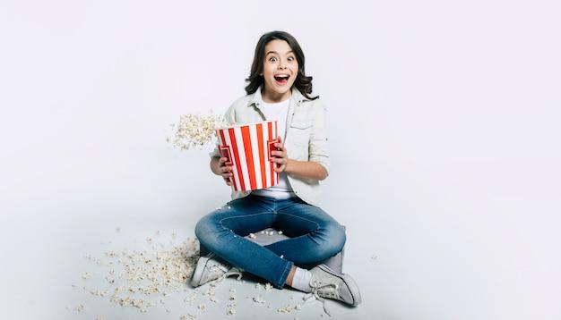 Сосредоточенный ребенок сидит в позе лотоса и ест попкорн, смотря мультфильмы или фильмы.