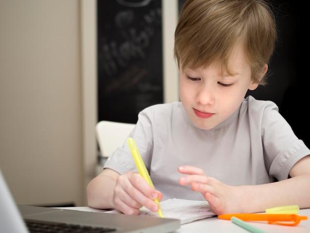 彼のノートのミディアムショットで書いて焦点を当てた子