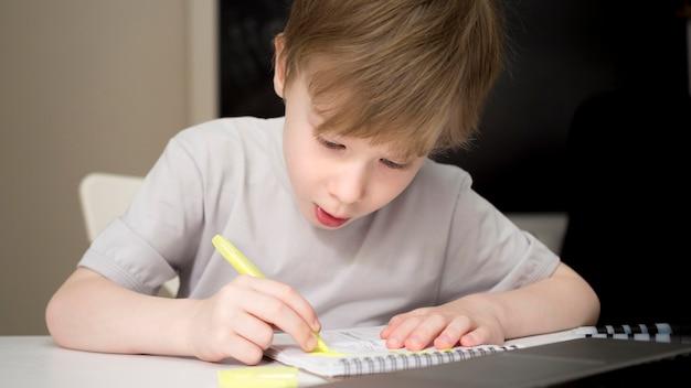 Сосредоточенный ребенок пишет в своей тетради