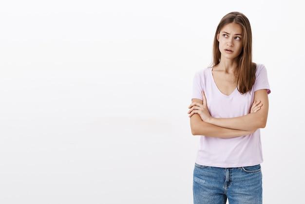Сосредоточенная невежественная, сбитая с толку привлекательная стильная молодая женщина, держащая руки, скрещенные на груди, приподнимает бровь, глядя в верхний левый угол, вспоминая ситуацию