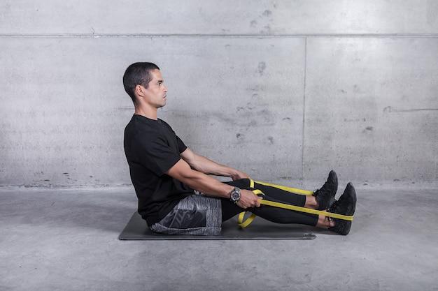 Сосредоточенный тренер показывает упражнение с резинкой