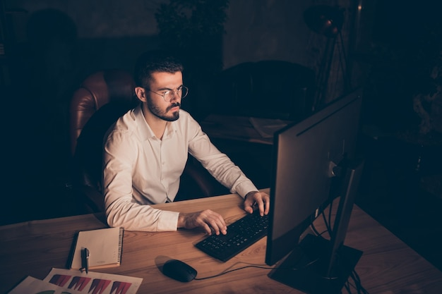 Focused concentrated man sitting at desktop typing computer